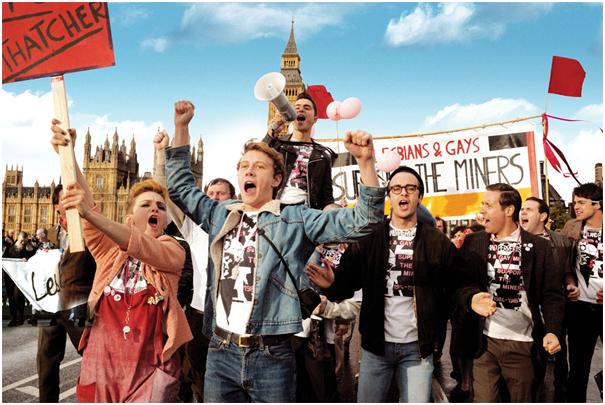 """Photographie extraite du film """"Pride!"""" mettant en scène le collectif LGSM lors d'une manifestation (Télérama). Source : http://www.telerama.fr/festival-de-cannes/2014/ils-incarnent-le-cinema-britannique-4-george-mackay-dans-pride,112866.php [consulté le 20/11/16]."""